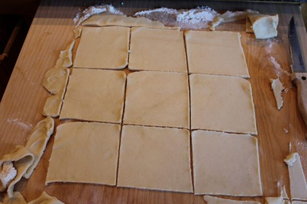 Christmas tarts cut dough into squares with a knife