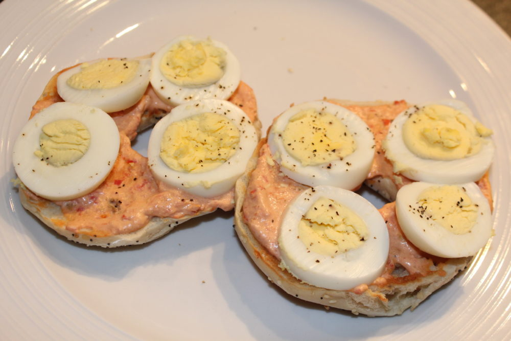Open faced breakfast bagel sandwich with Tomato Chili cream cheese and hard-boiled egg slices