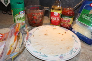 Ingredients for easy Pizza Tortilla Roll recipe include olive oil, onion, red pepper, mushrooms, tortillas, pizza sauce, mozzarella cheese, parmesan cheese. An easy recipe for 1-4 people.
