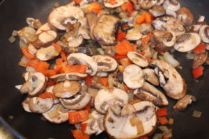 Saute mushrooms, onions, red peppers in olive oil in a frying pan to prepare the veggies for the Pizza Tortilla Roll recipe. An easy recipe that can be made for 1-4 people.