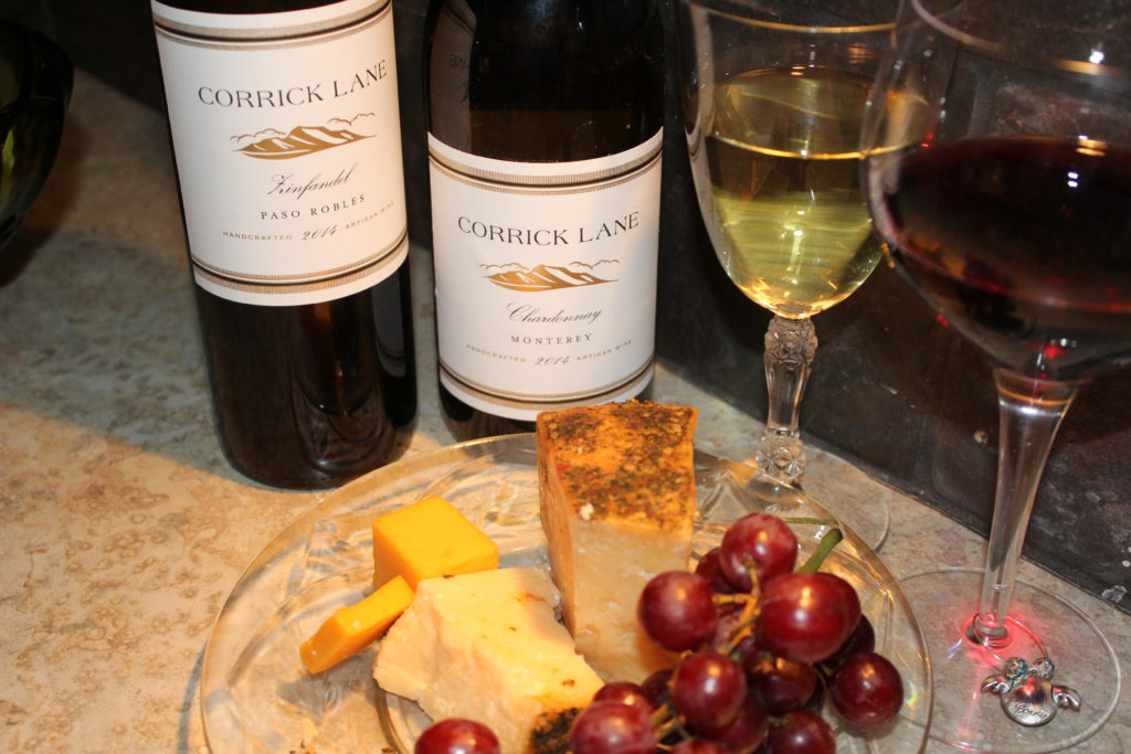 St. Urho's Day and Wine Club Review. Wine glass of Chardonnay wine and red Zinfandel wine with bottles of wine and parmesan and cheddar cheese, grapes