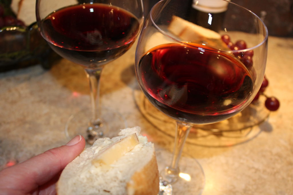 St. Urho's Day and Wine Club Review. Wine glasses with french bread, parmesan cheese and snack visible through wine glass