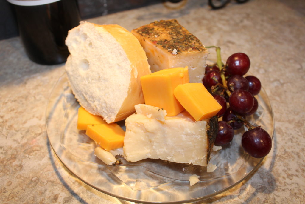 St. Urho's Day and Win Club Review. Wine with close up of plate of Mediterranean parmesan cheese, Wisconsin cheddar cheese, french bread, grapes