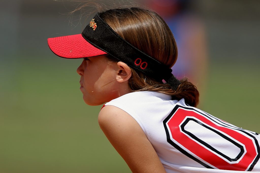 Young girl playing softball. Parent tip to save money for kids for college.
