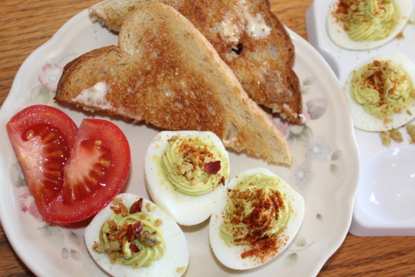 Plate with Scrumptious Spicy Avocado Deviled eggs, tomato slices, and toast