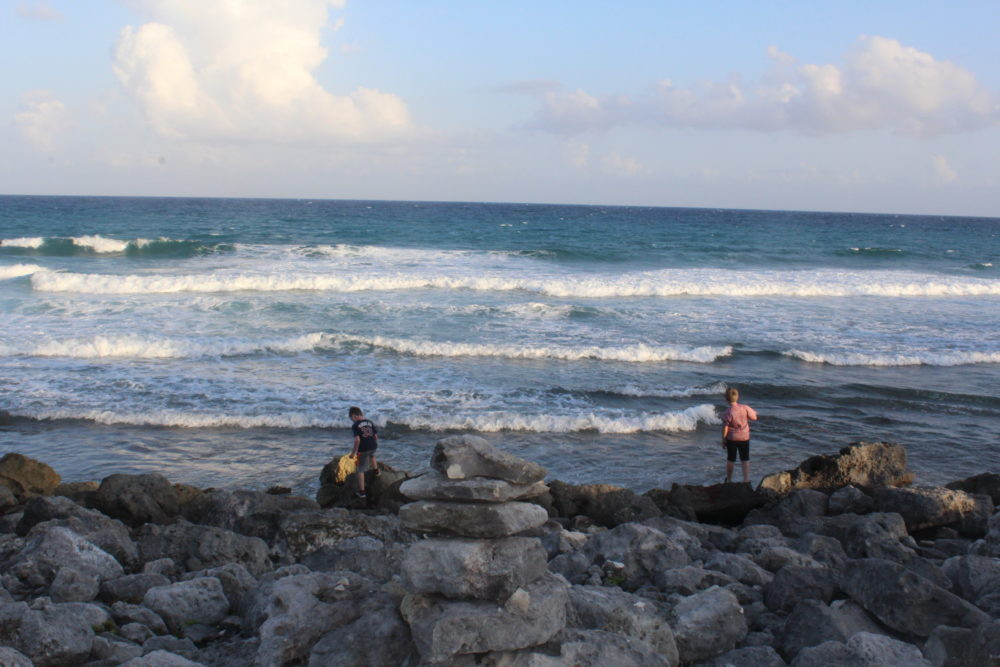 Kids traverse the rocky sea shore. Palladium All-inclusive resort Riviera Maya, Mexico.