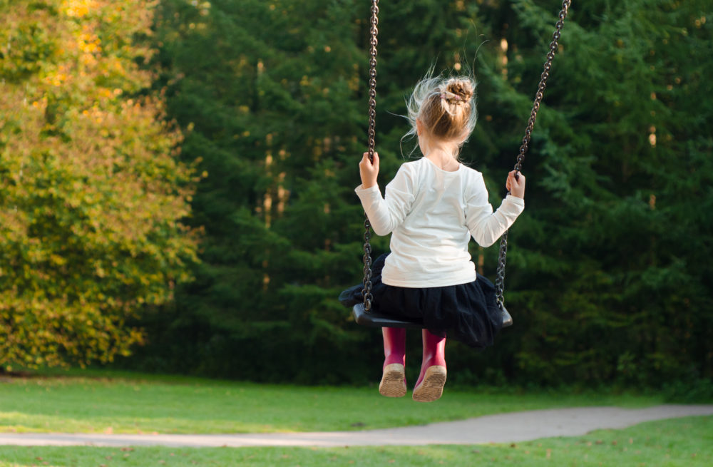 Girl on a swing by a forest by Pexels.