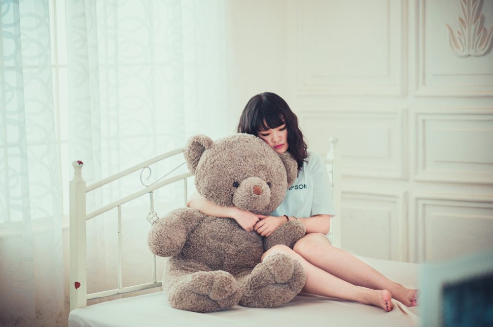 Teen girl hugging a teddy bear.