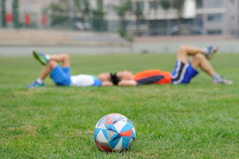 Boys lounging on a soccer field.