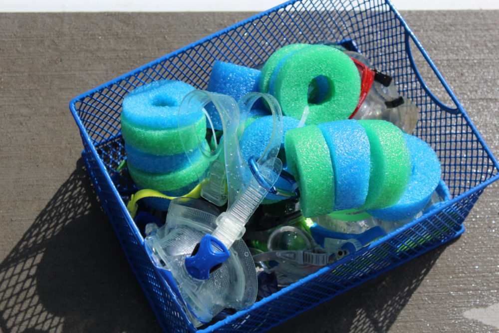 DIY Pool Noodle Goggle Floats in goggle basket by pool