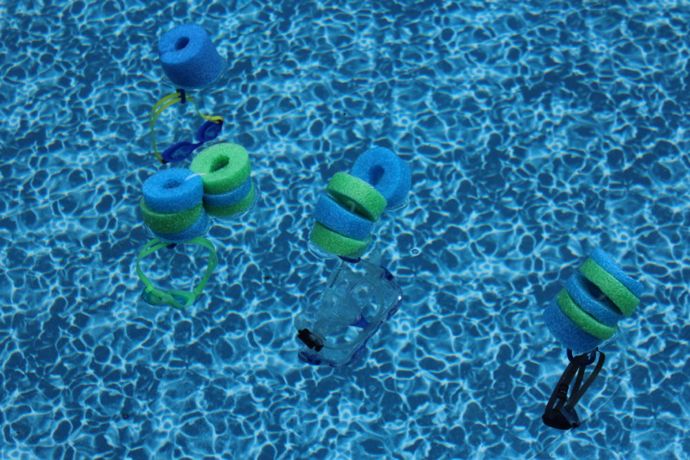 Pool Noodle Goggle Floats floating in pool holding goggles