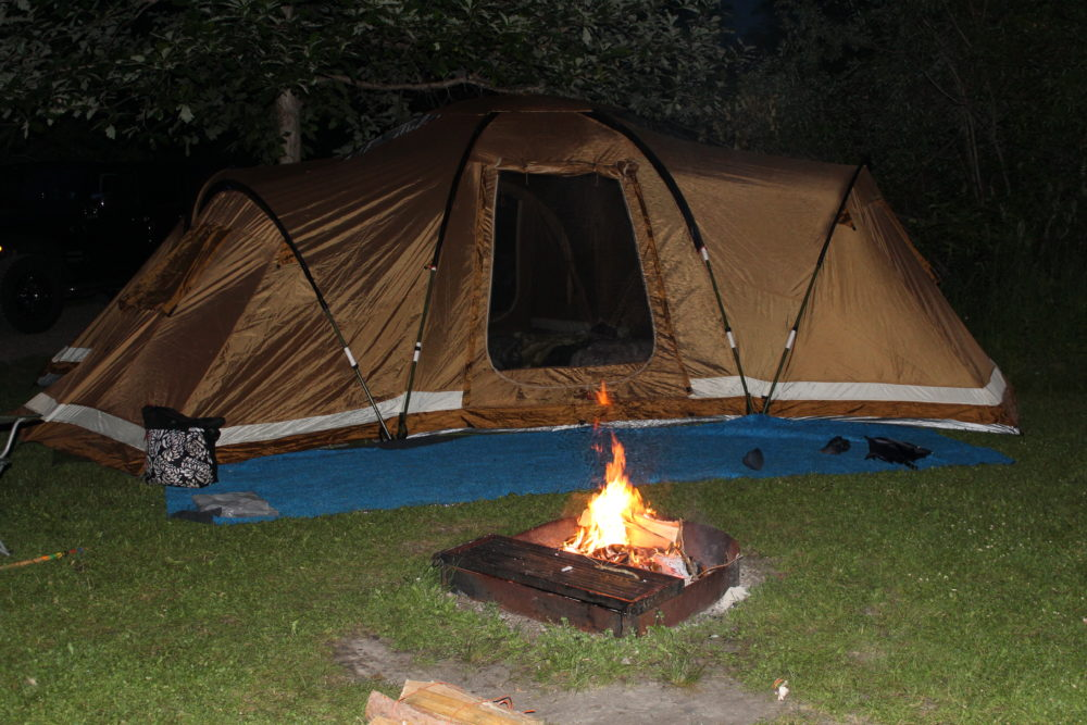 Tent and bonfire at night. 20 things make family camping easier