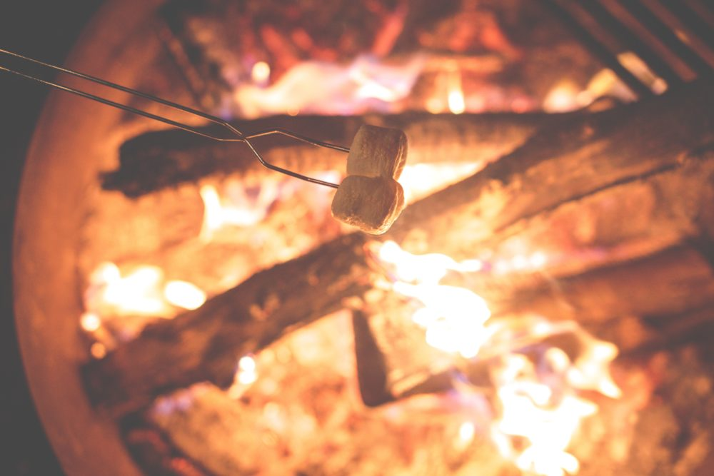 Family camping essentials. Cooking smores over the campfire with roasting stick. 20 things make family camping easier