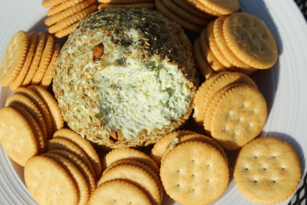 Jalapeno Chia and Pumpkin Seed Cheese Ball closeup with some cheese scooped out. vegetarian appetizer | appetizer recipe | appetizers for a crowd | summer entertaining | holiday entertaining | party food