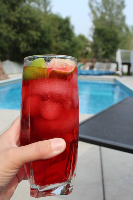 Wild Strawberry Iced Tea by the pool with lime wedges