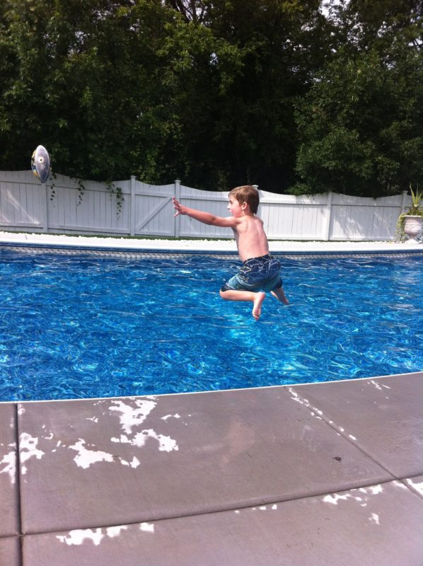 Jumping into a swimming pool trying to catch a football. Family fun while exercising too. 6 Tips to make exercise more fun for the family. #familyfun #exercising #healthylifestyle #famiytime #swimming #swimmingpool #family