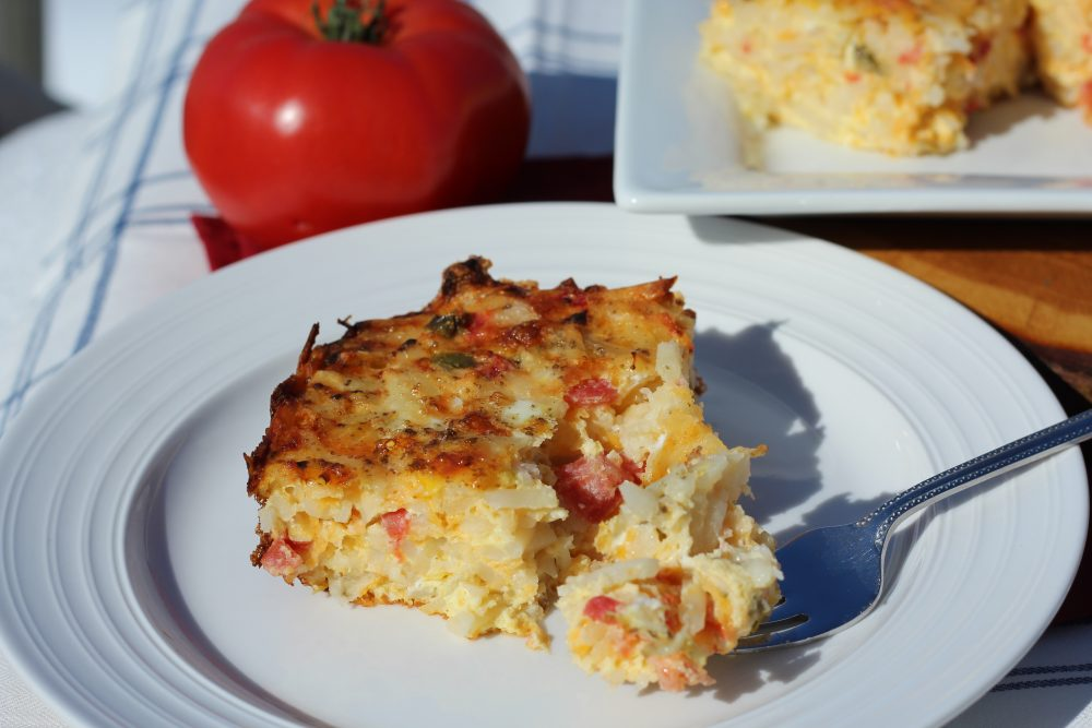 Spicy Comfort Food Baked Hash Brown Casserole Vegetarian piece egg bake casserole dish. #hashbrowncasserole #mealprep #cookingtips #hashbrownrecipes #hashbrownbreakfastcasserole #cheesyhashbrowncasserole #eggbake #eggbakecasserole #eggbakerecipes #eggbakewithhashbrowns #breakfastrecipes #brunchideas #juliehoagwriter #recipeideas #hybridrecipe