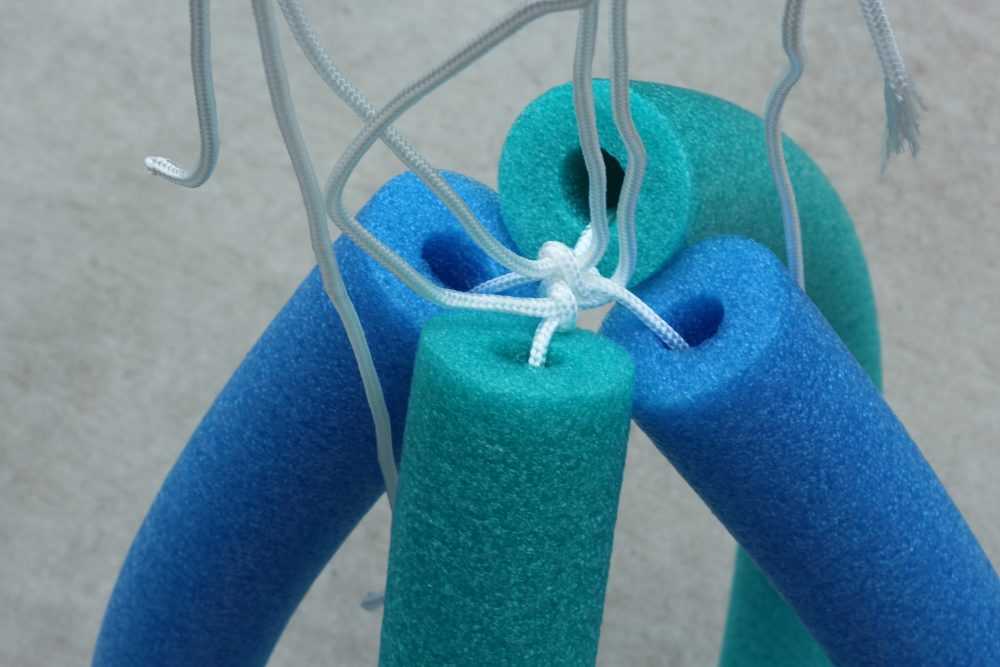 String rope through 2nd pool noodle and wrap over first noodle and tie rope in a knot