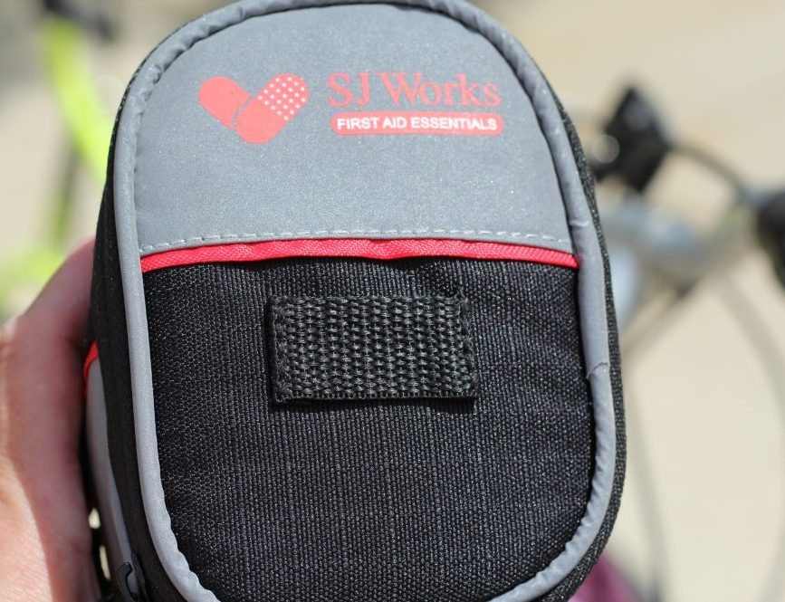 Helpful Practical First Aid Bag for Safer Biking. Two different styles available. One has a cell phone slot and ear phone slot. Both contain first aid essentials perfect for moms, dads, parents taking their kids bicycling. #bike #biking #firstaidkit #firstaidbag #moms #safety