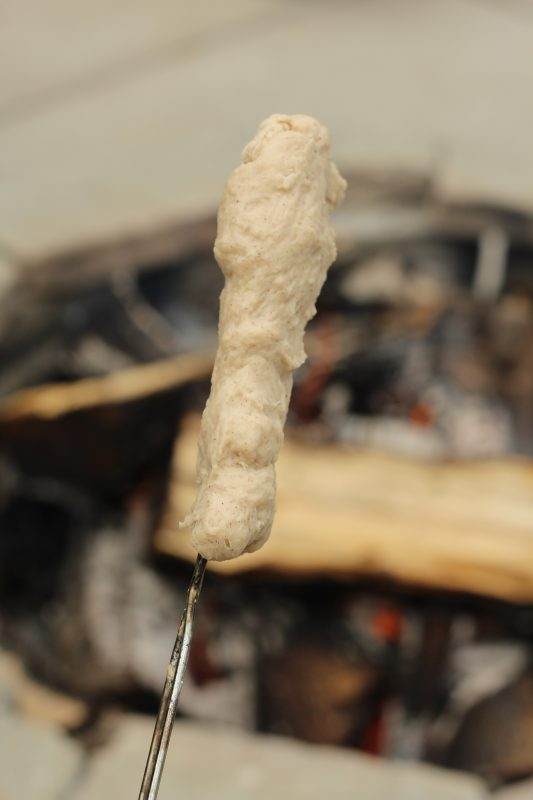Campfire Cooking Cinnamon Breadsticks Recipe for Camping and Backyard Bonfires Bannock bread dough on roasting stick