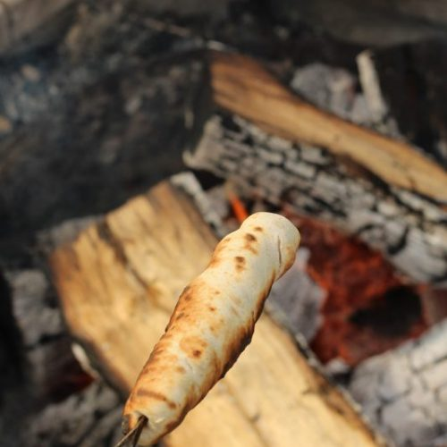 Campfire Cooking Cinnamon Breadsticks Recipe for Camping and Backyard Bonfires browned bannock bread. Cooking over an open fire.