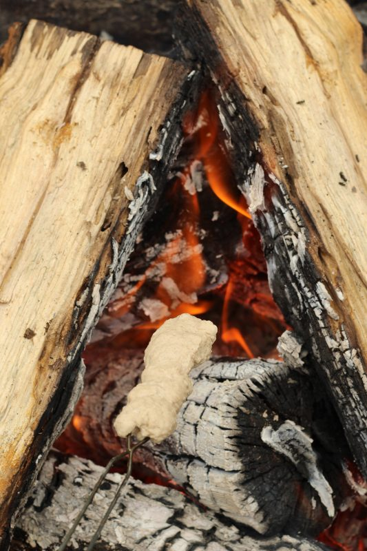 Campfire Cooking Cinnamon Breadsticks Recipe for Camping and Backyard Bonfires cooking dough over fire.