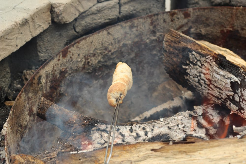 Campfire Cooking Cinnamon Breadsticks Recipe for Camping and Backyard Bonfires roasting bread dough over fire.