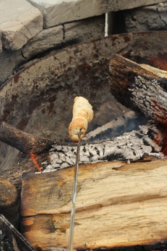 Campfire Cooking Cinnamon Breadsticks Recipe for Camping and Backyard Bonfires roasting bread over bonfire.