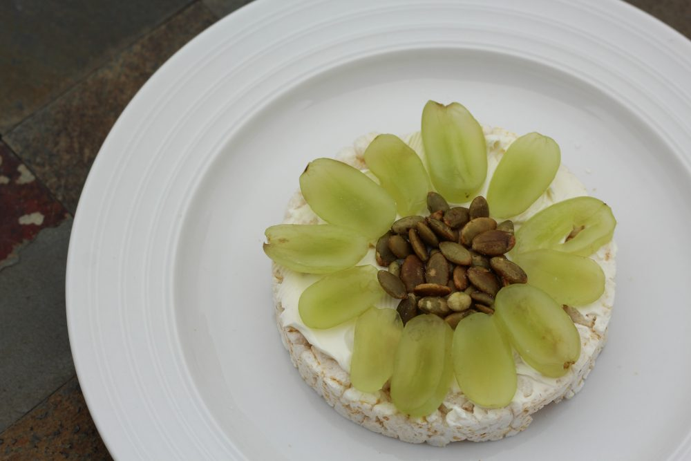 Cream cheese, green grapes, pepitas on top of a plain rice cake flower design light breakfast or snack