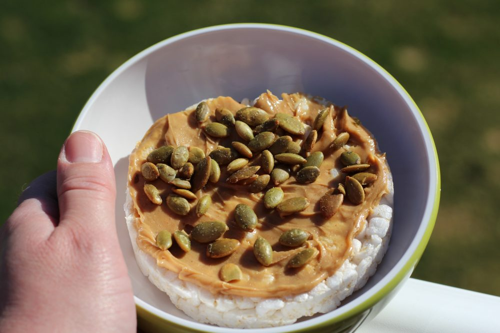 LIght meal ideas. Peanut butter and pepitas on a plain rice cake low carb