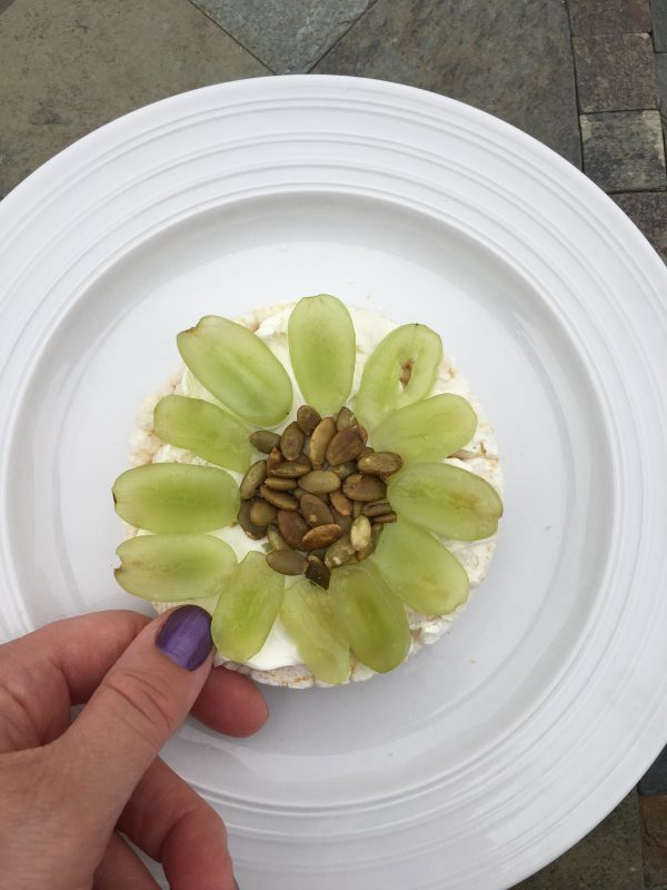 Ten Healthy Recipes for Rice Cake Toppings. Cream cheese, green grapes, pepitas on top of a plain rice cake flower design light breakfast or snack