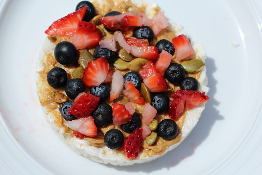10 recipes to top rice cakes with including Rice cake topping with strawberries, peanut butter, blueberries, pumpkin seeds for a light meal or snack.