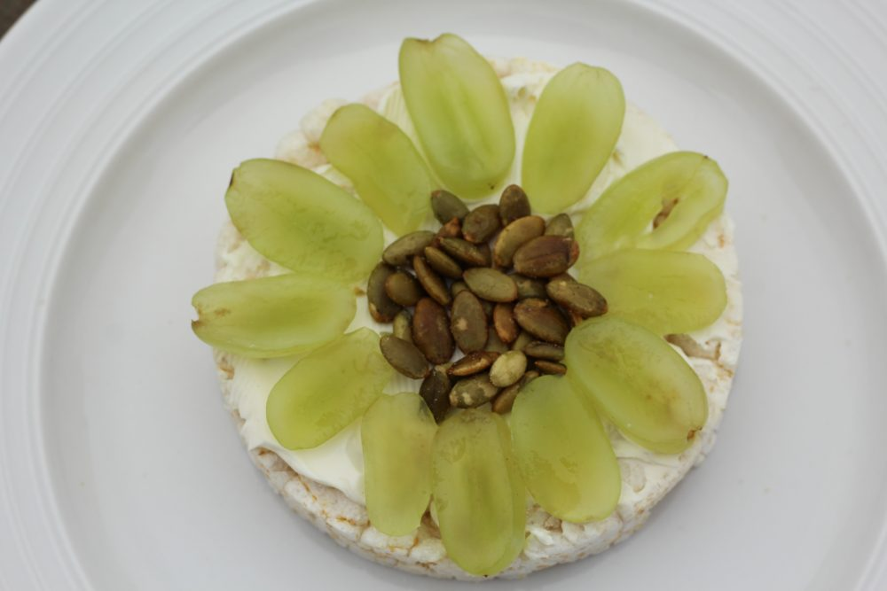 Light meal with a rice cake. green grapes, pepitas, cream cheese rice cake topping light meal low carb