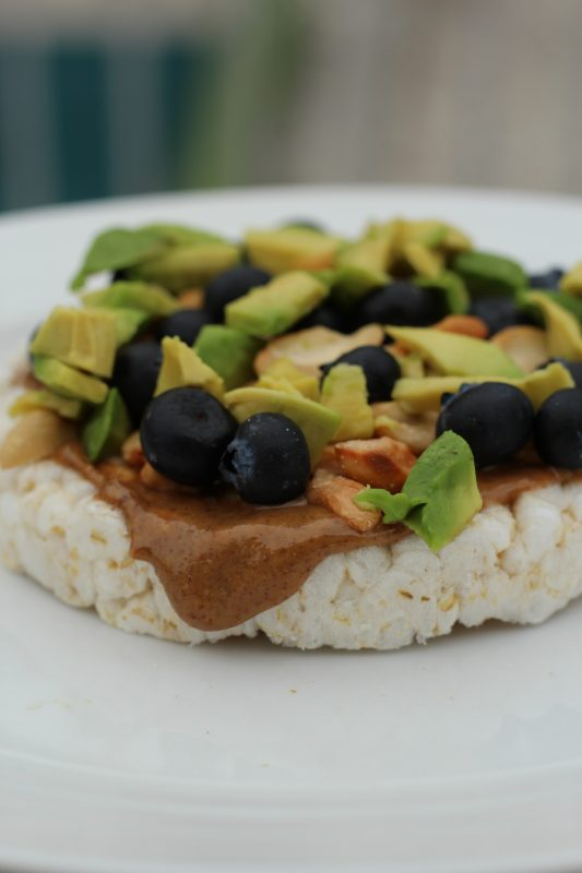 Rice cake topping for a light meal or snack. Almond butter, blueberries, avocado, cashews topping for a rice cake a healthy light meal