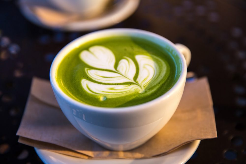 Benefits of Matcha tea and weight loss. Green matcha tea with a heart flower in white on top of the tea, in a white mug.