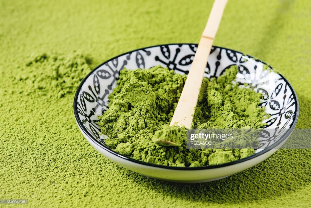 Benefits of matcha tea and weight loss and healthy benefits of tea. Green matcha tea in a blue and white bowl.
