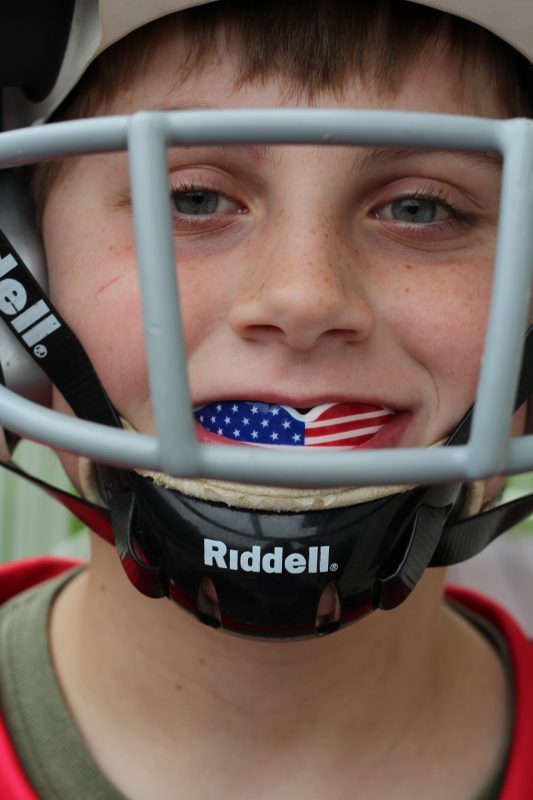 Boy with a flag mouthguard in his mouth and a football helmet