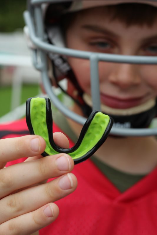 boy in a football helmet smiling holding a green mouthguard