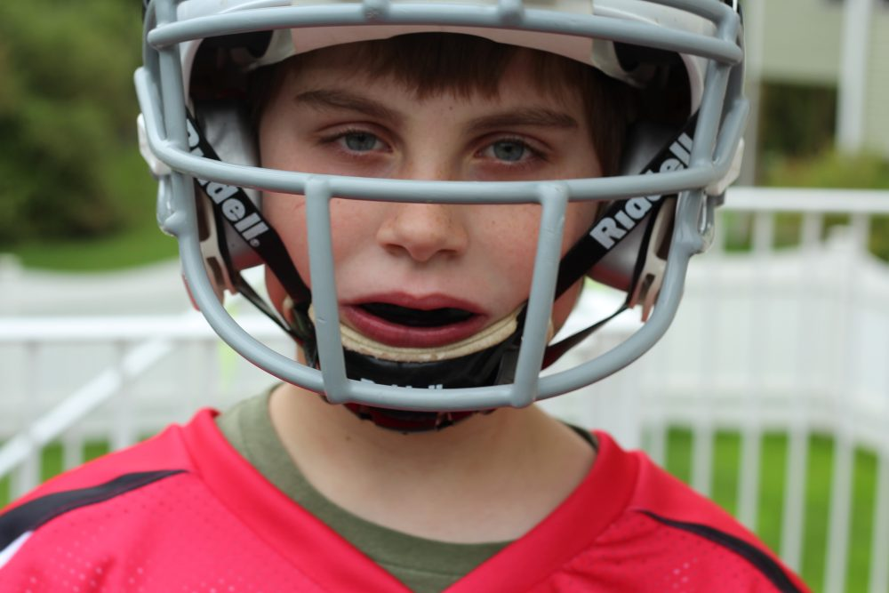 child with a football helmet and mouthguard in