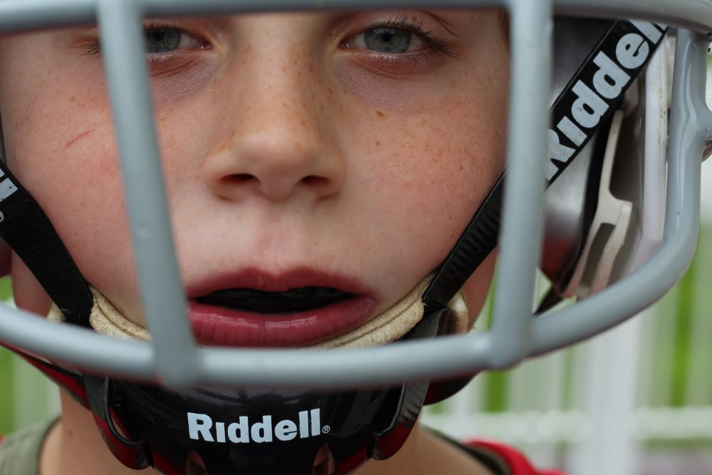 child with a mouthguard in and football helmet on