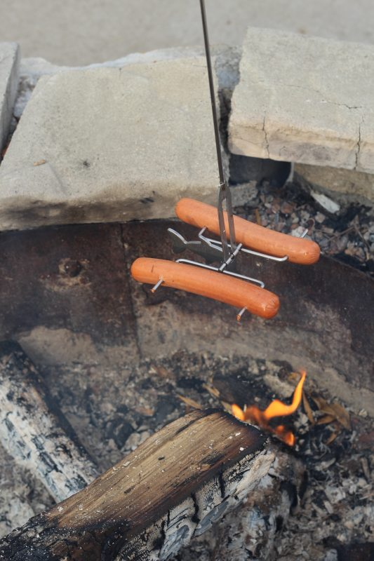 Family camping and Roasting hot dogs on a fire fishing pole stick over a fire