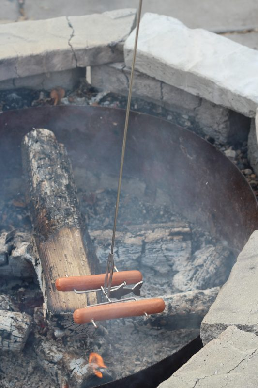 Family camping hack for cooking hot dogs over a bonfire with a roasting stick using a fishing pole stick.