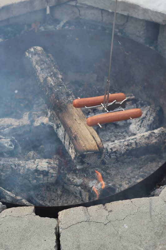 cooking hot dogs over a campfire with fire fishing pole stick roaster