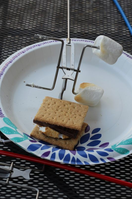 Family camping and making smores with fire fishing pole roasting stick