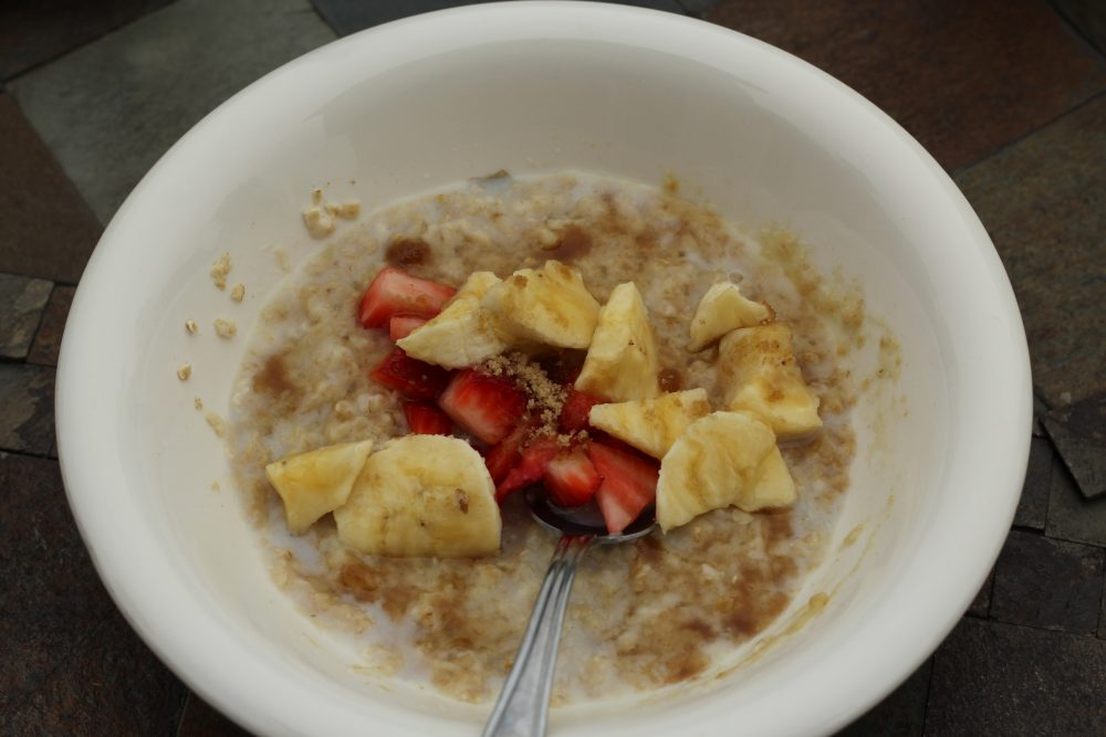 Oatmeal topped with bananas and strawberries, brown sugar, and honey