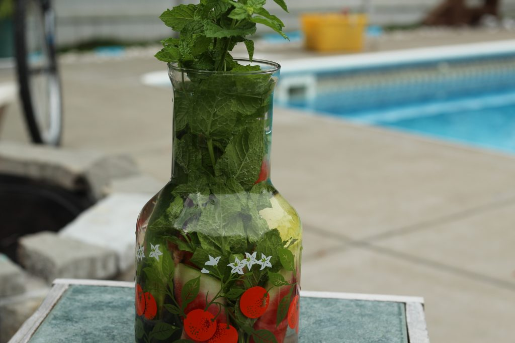 watermelon infused water with mint leaves and cucumber spears to enjoy in your backyard or poolside